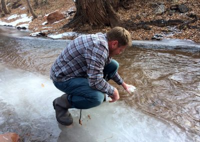 Colorado Springs Utilities environmental technician Corey Thiel collects chilly water samples for testing. Photo by Holly Pretsky