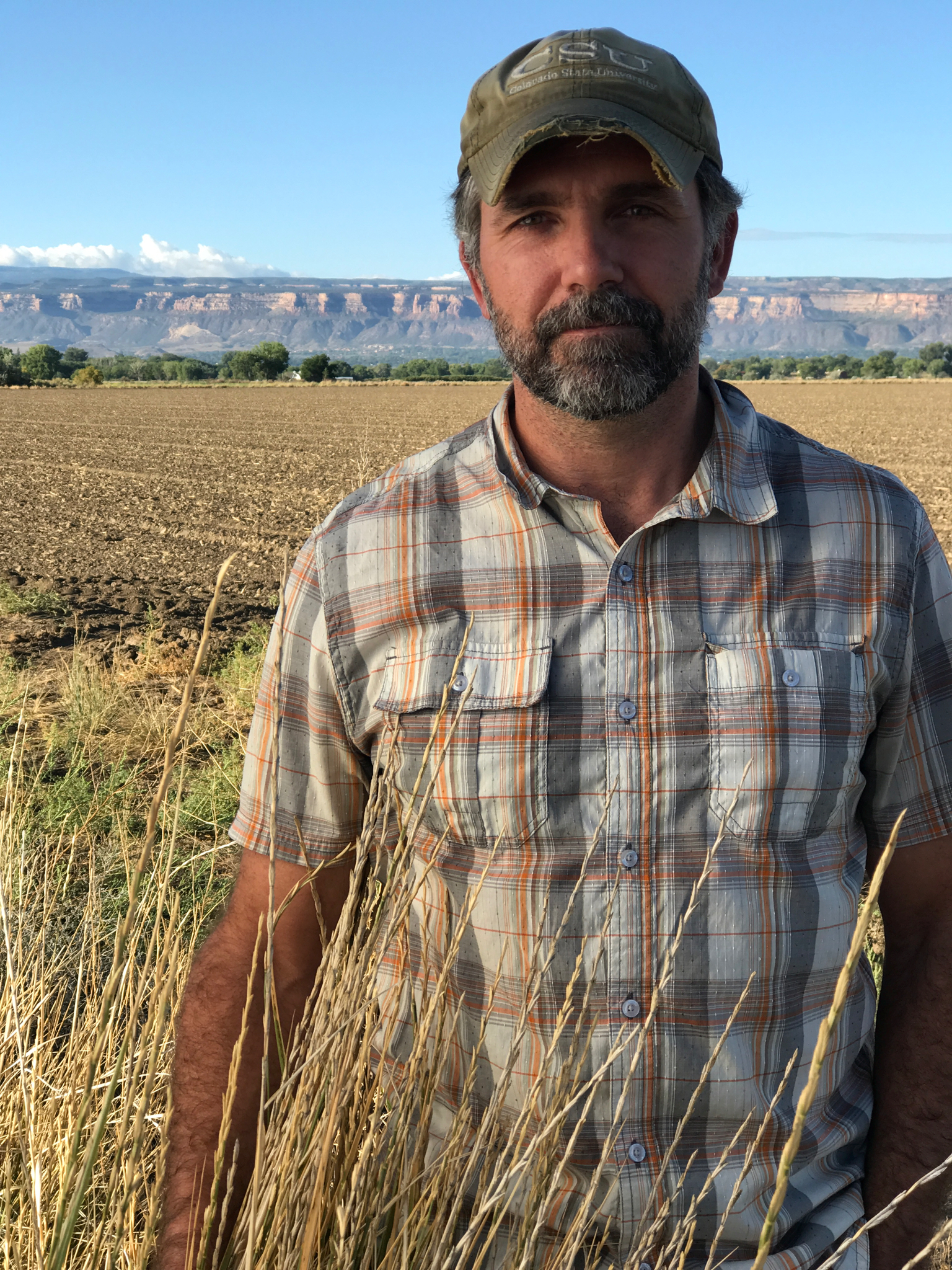 Perry Cabot stands in a fallowed field near Grand Junction