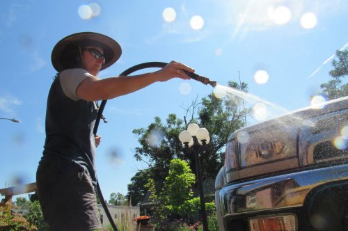 A Denver resident who asked that her name not be used washes her car in the Berkeley neighborhood July 12, 2019. It is one of dozens of neighborhoods in Denver whose water is delivered via lead service lines.