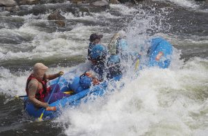 Rafters and surfers enjoy riding a wave on the Gunnison River near Gunnison, Colo., on May 17, 2020. The Gunnison is flowing at about 80 percent of its normal volume for this time of year. Overall, Colorado's snowpack is melting faster than usual. Along with lower river flows the presence of COVID-19 is creating challenges for commercial river running companies as well as private boaters. Credit: Dean Krakel/Special to Fresh Water News